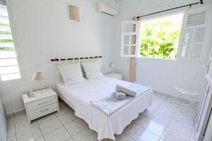 La Petite Villa Guadeloupe - villa A - Chambre 2 climatisée donnant sur le jardin à l'arrière de la maison