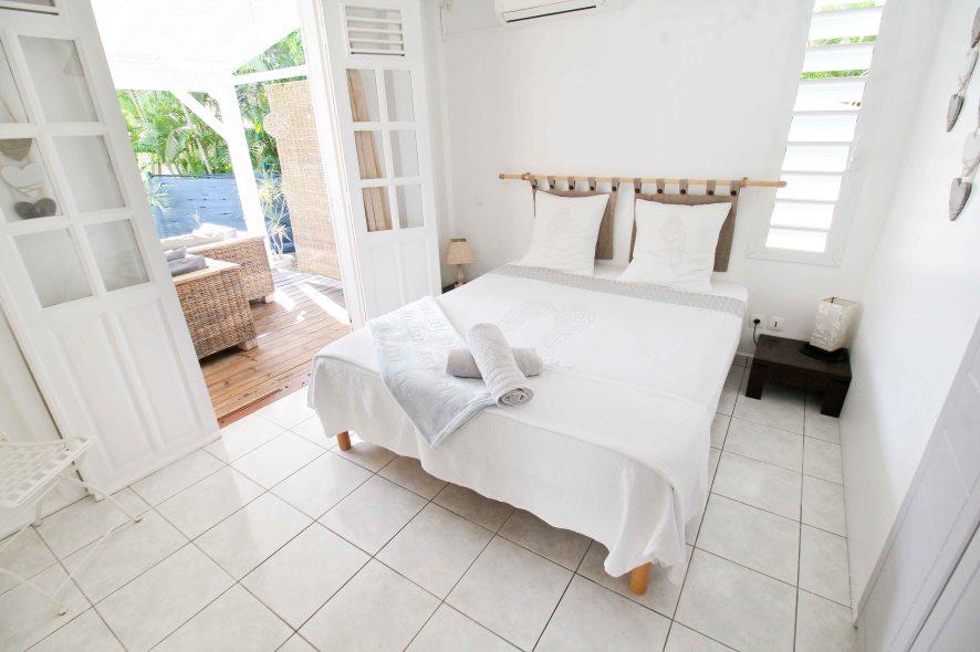 La Petite Villa Guadeloupe - villa A - Chambre 1 climatisée donnant sur la terrasse - vue sur la piscine